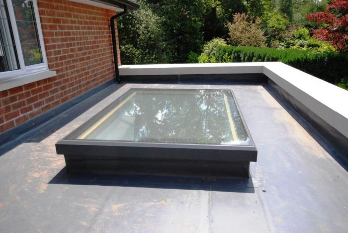 Flat roof lantern on Sarnafil roof with stone coping to parapet